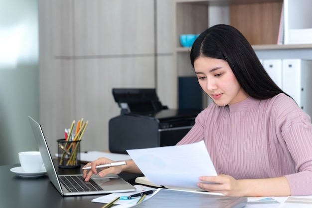 Levensstijl mooie aziatische zakelijke jonge vrouw met laptopcomputer en slimme telefoon op kantoor