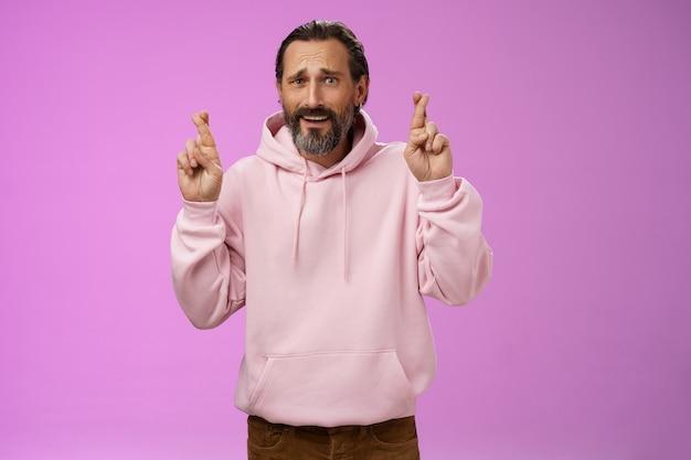 Levensstijl. nerveus onzekere hoopvolle knappe bebaarde 40s man in roze stijlvolle hoodie ineenkrimpen bezorgde crossfigers veel geluk wensen hoop dat ze geen baan verliezen smeken biddend droom die uitkomt.