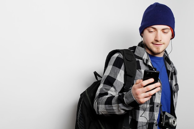 Levensstijl, onderwijs en mensenconcept: jonge man die naar muziek luistert en smartphone gebruikt, terwijl hij tegen een grijze achtergrond staat.