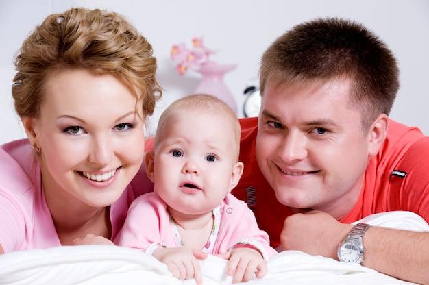 Levensstijl portret van de mooie jonge en gelukkige familie liggend in bed thuis