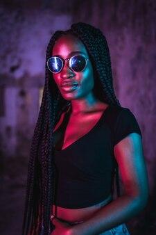 Levensstijl portret van een jonge zwarte vrouw met lange vlechten zonnebril en een zwart t-shirt roze en blauwe neonlichten stedelijke fotografie van een valdanser in ernstige pose
