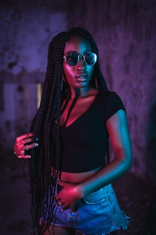 Levensstijl portret van een jonge zwarte vrouw met lange vlechten zonnebril en een zwart t-shirt roze en blauwe neonlichten stedelijke fotografie van een valdanser zijwaarts op zoek