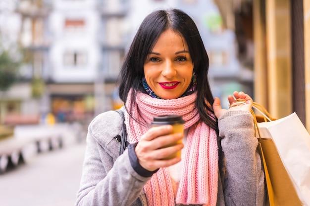 Levensstijl, portret van een mooi kaukasisch meisje dat in de stad winkelt met papieren zakken en een afhaalkoffie