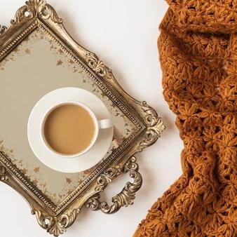 Levensstijl samenstelling met kopje koffie met melk op vintage gouden dienblad en gebreide bruine deken plaid op witte achtergrond. plat leggen