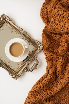 Levensstijl samenstelling met kopje koffie met melk op vintage gouden dienblad en gebreide bruine deken plaid op witte achtergrond.