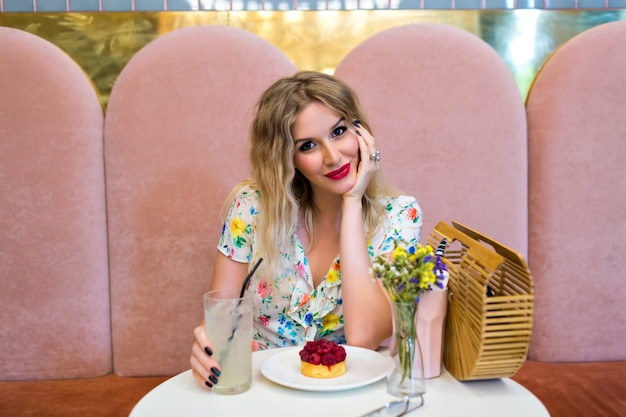 Levensstijl schattig beeld van mooie blonde vrouw poseren, zitten en genieten van haar maaltijd, kijken op camera, elegante bloemenjurk en lichte make-up, frambozencake eten