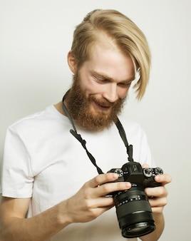 Levensstijl, technologie en mensenconcept: professionele fotograaf. portret van zelfverzekerde jonge man in shirt met camera over witte ruimte