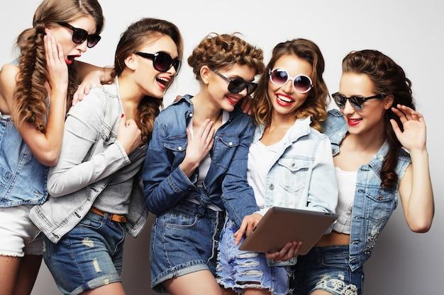Levensstijl, technologie en mensenconcept: vijf hipstermeisjesvrienden die selfie met digitale tablet nemen