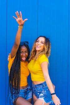 Levensstijl, tienermeisje vrienden genieten van in de fotoshoot op een blauwe muur gekleed in gele t-shirts. zwart meisje met lange vlechten en blond kaukasisch meisje.