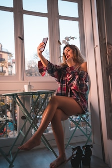 Levensstijl van een jong blond ontbijt aan het ontbijt naast de verkoop van zijn huis. gekleed in ondergoed en pyjama, het uitvoeren van een selfie