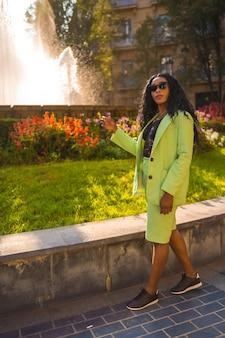 Levensstijl van een jong meisje van zwarte afrikaanse etniciteit met een prachtig groen pak. de toerist zat in een prachtige waterbron