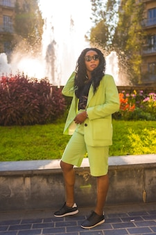Levensstijl van een jong meisje van zwarte afrikaanse etniciteit met een prachtig groen pak en zonnebril. de toerist zat in een prachtige waterbron