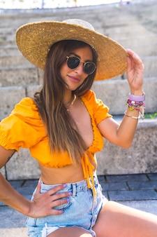 Levensstijl van een jonge blanke brunette die in de zomer in een park in de stad loopt. portret van het meisje dat lacht met een hoed bij zonsondergang Premium Foto
