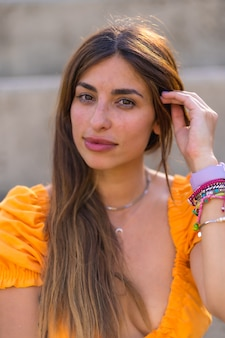 Levensstijl van een jonge blanke brunette die in de zomer in een park in de stad loopt. portret van het meisje dat naar de camera kijkt en glimlacht Premium Foto