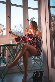 Levensstijl van een jonge blonde vrouw die ontbijt naast de verkoop van haar huis. gekleed in ondergoed en pyjama, met een koffiedrankje en een selfie
