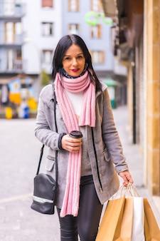 Levensstijl van een kaukasisch donkerbruin meisje dat in de stad winkelt met papieren zakken en een afhaalkoffie