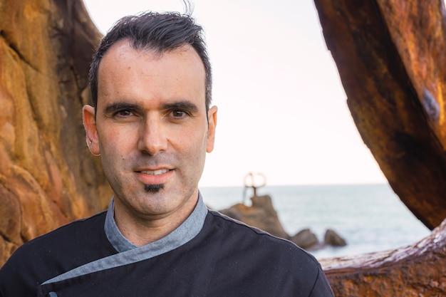 Levensstijl van een kok, portret van blanke kok met zwarte schort in een foto op de kust