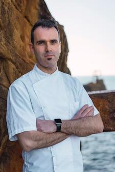 Levensstijl van een kok, portret van een jonge man in een witte schort in een foto op de kust