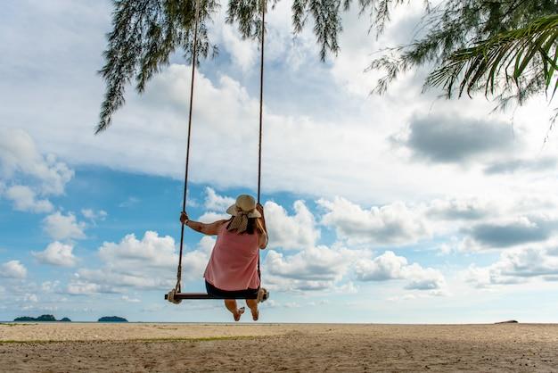 Levensstijl van jong gelukkig meisje op schommel op het overzeese strand in tropisch eiland, reizend en ontspannend concept.