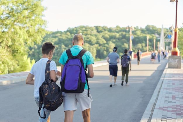 Levensstijl van jonge mannen, tieners met rugzakken lopen hun rug