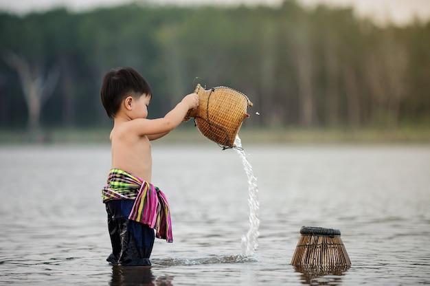 Levensstijl van vissersjongen in rivier op het platteland van thailand