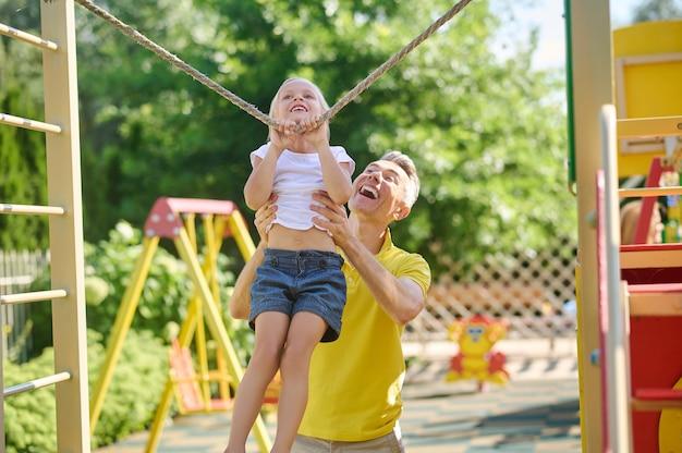 Levensstijl. vrolijke aantrekkelijke man in geel t-shirt ter ondersteuning van kleine energieke dochter die op een zomerdag op een koord op de speelplaats traint
