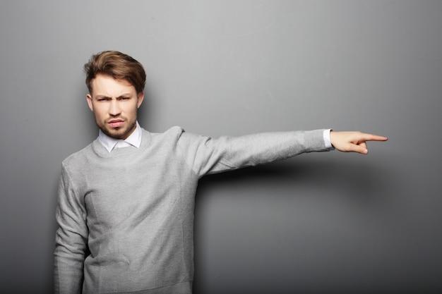 Levensstijl, zaken en mensen concept: trieste zakenman laat iets zien over grijze ruimte