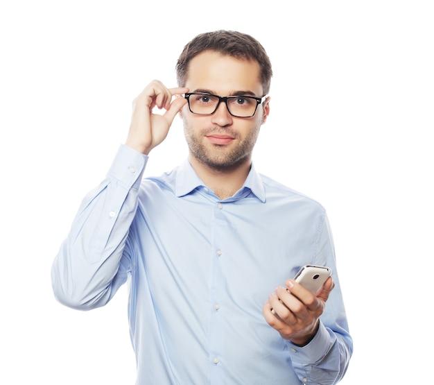 Levensstijl, zaken en mensenconcept: jonge bedrijfsmens die mobiele telefoon met behulp van.