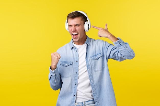 Levensstijl zomervakantie technologie concept vrolijke knappe man in vrijetijdskleding luisteren muziek in koptelefoon wijzend op oortelefoon als genieten van mooie beats en geweldig lied gele muur