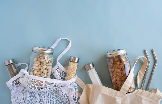 Levensstijl zonder afval. katoenen netzak met moer, kruiden in duurzame glazen pot en herbruikbaar stro op blauwe achtergrond