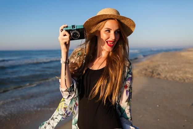 Levensstijl zonnig portret van jonge schoonheid fotograaf vrouw poseren in de buurt van eenzaam strand aan de voorkant van de oceaan stijlvolle bikini hoed zonnebril en pareo, luxe vakantie vibes.