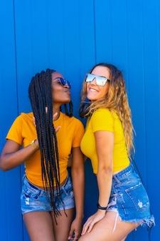Levensstijl, zwart meisje en blonde blanke meisje in gele jurken. erg blij en lachend met muziekhoofdtelefoons en zonnebril
