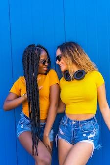 Levensstijl, zwart meisje en blonde blanke meisje in gele jurken. vrienden met een veelbetekenende blik, erg blij en lachend met muziekkoptelefoons en zonnebril