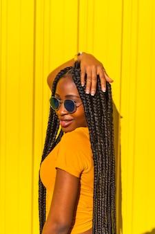 Levensstijl, zwart meisje met lange vlechten, gele t-shirts en korte spijkerbroek op een gele muur. modieuze pose van de aantrekkelijke met verleidelijke blik, straatfotografie