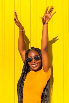 Levensstijl, zwart meisje met lange vlechten, gele t-shirts en korte spijkerbroek op een gele muur. modieuze pose van de aantrekkelijke met verleidelijke blik