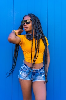 Levensstijl, zwart meisje met lange vlechten, in geel t-shirt en zonnebril. sexy meisje en dj met koptelefoon glimlachen