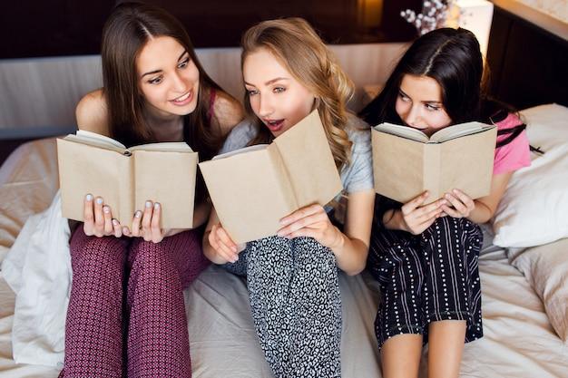 Levensstijlbeeld van drie beste vrienden in pyjama's die boeken lezen, studeren en gesprekken voeren in de slaapkamer. groep studenten huiswerk samen thuis. gezellige warme kleuren. emotionele gezichten.