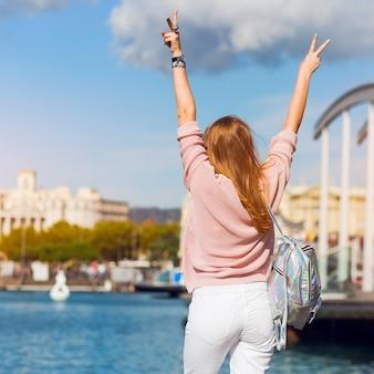 Levensstijlbeeld van hipstermeisje in lente pastelkleuruitrusting, trendy juwelen, rode lippen die van vakantie in barcelona genieten.