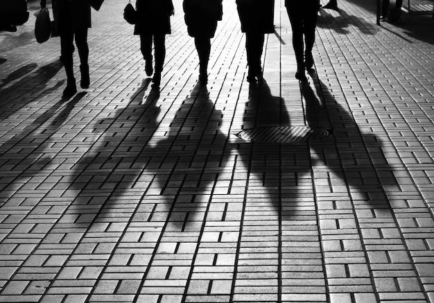 Levensstijlconcept. licht en schaduwen in de stad. silhouetten van mensen die door de straten van een grote stad lopen en verlicht door tegenlicht. schaduwen van mensen die in avondlicht op straat lopen.