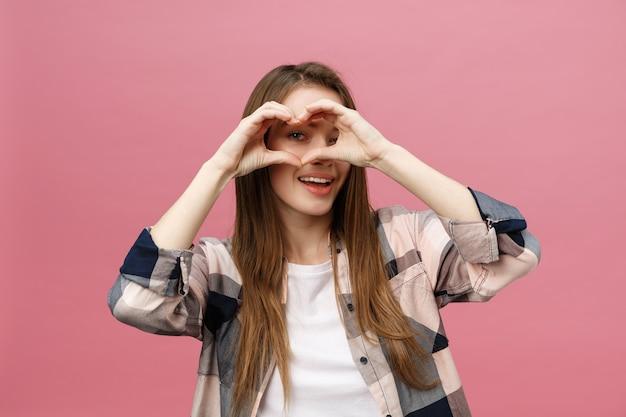 Levensstijlconcept: mooie aantrekkelijke vrouw die in wit overhemd een hartsymbool met haar handen maken