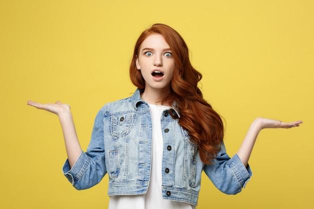 Levensstijlconcept: verraste jonge vrouw met hand aan kant over gouden gele achtergrond