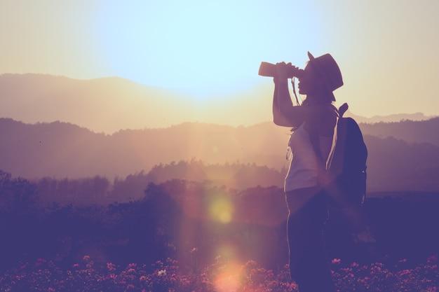 Levensstijlmeisje die pret hebben in de avond met reisverrekijkers, reisideeën.