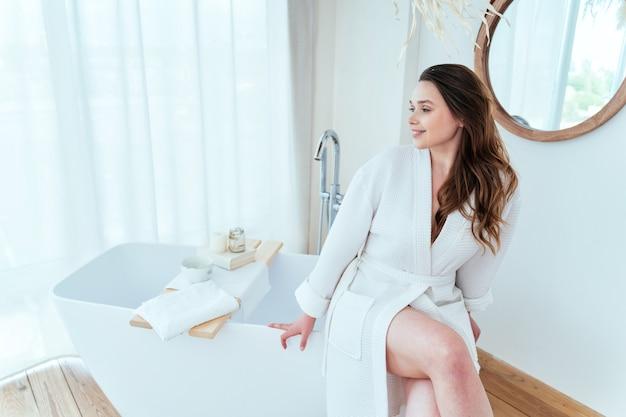 Levensstijlmomenten van een jonge vrouw thuis vrouw die tijd doorbrengt in de badkamer