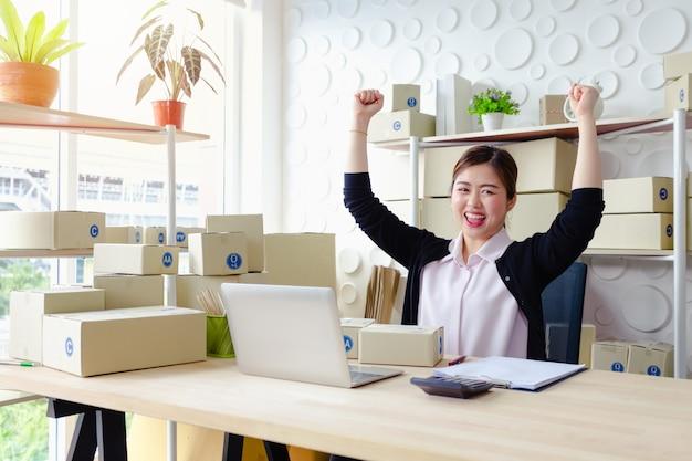Levensstijlondernemers die in bureau zitten die het schermlaptop glimlachen glimlachen die, kleine onderneming kmo werken