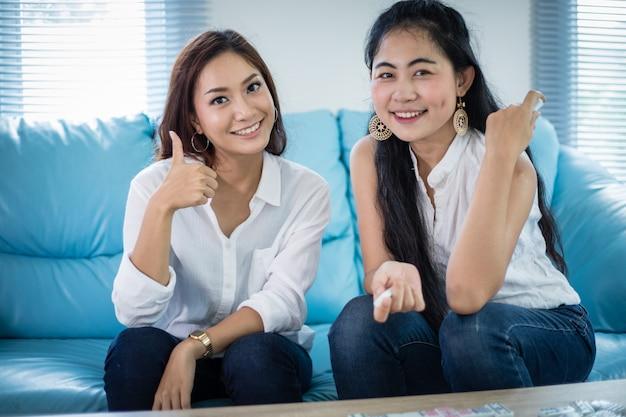 Levensstijlportret aziatische vrouwen van beste vrienden - gelukkig glimlachen op bank bij woonkamer
