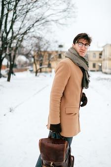 Levensstijlportret van de knappe mens in het elegante kleren stellen openlucht in de winterstraat