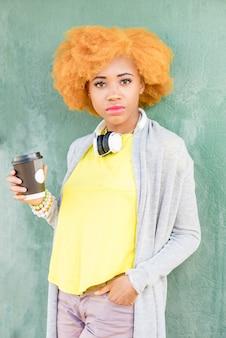 Levensstijlportret van een afrikaanse vrouw in vrijetijdskleding die zich met koffie op de groene muurachtergrond bevindt