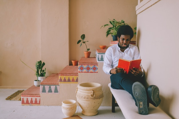 Levensstijlportret van het jonge donkerhuidige boek van de mensenlezing