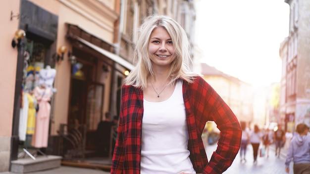 Levensstijlportret van modieuze gelukkige blonde met slordig haarmeisje die een rotsrood overhemd, wit t-shirt dragen dat pret buiten in de stad heeft