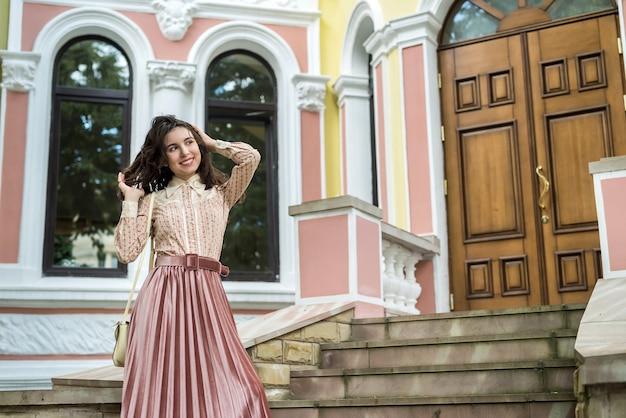 Levensstijlportret van mooie dame dichtbij huis op de stadsstraat